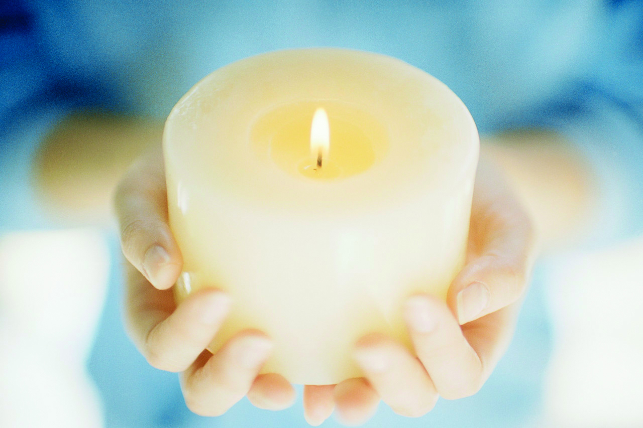 Memorials: Hands Holding a Lit Candle